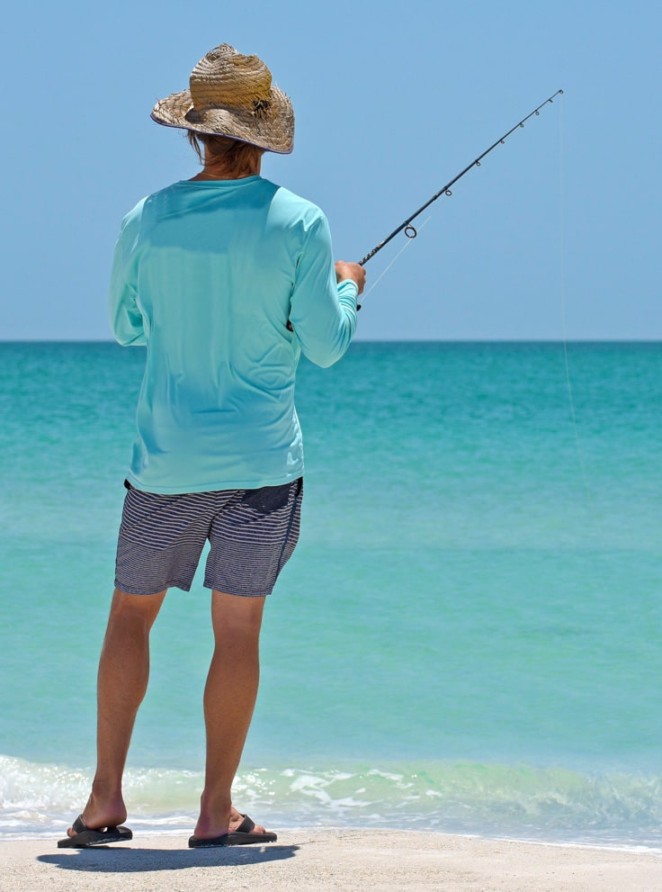 An unidentified local young man on the beach fishing in the shallow water of the Gulf of Mexico.