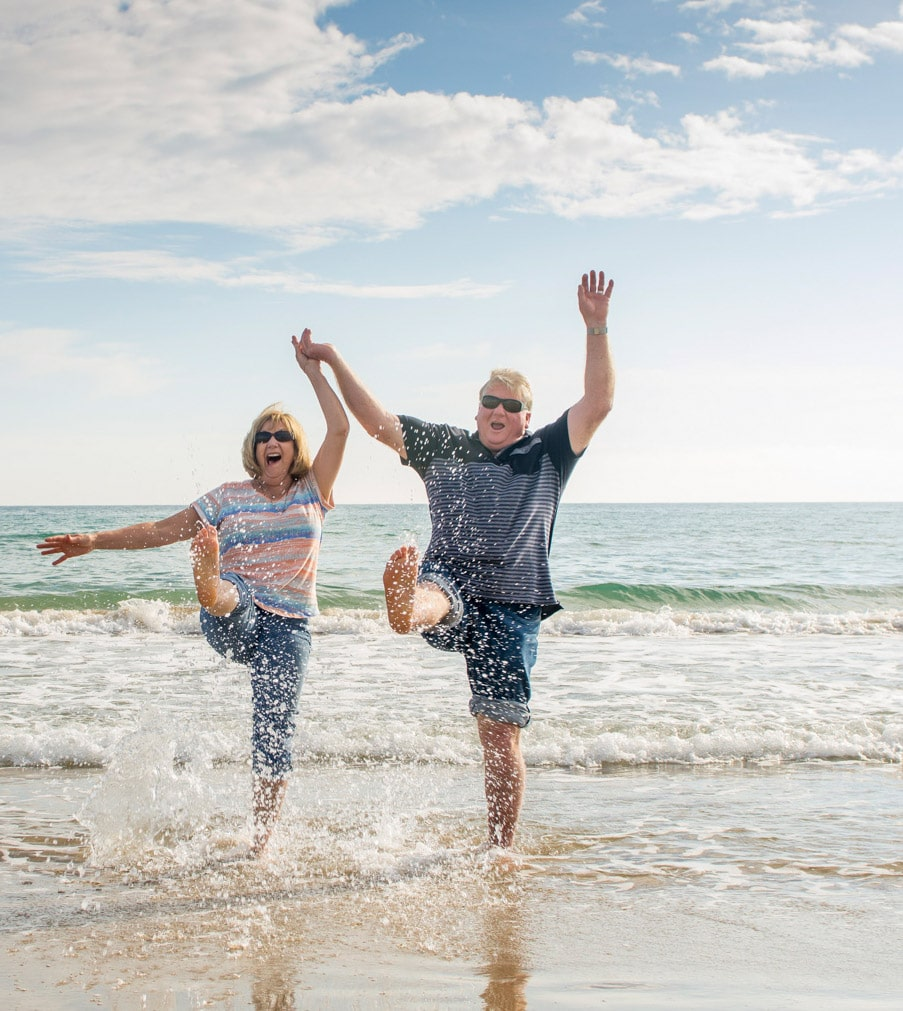 Happy senior couple enjoying retirement lifestyle having fun walking on the beach in a sunny beautiful day holding hands and hugging each other while traveling around Europe. In active old People.