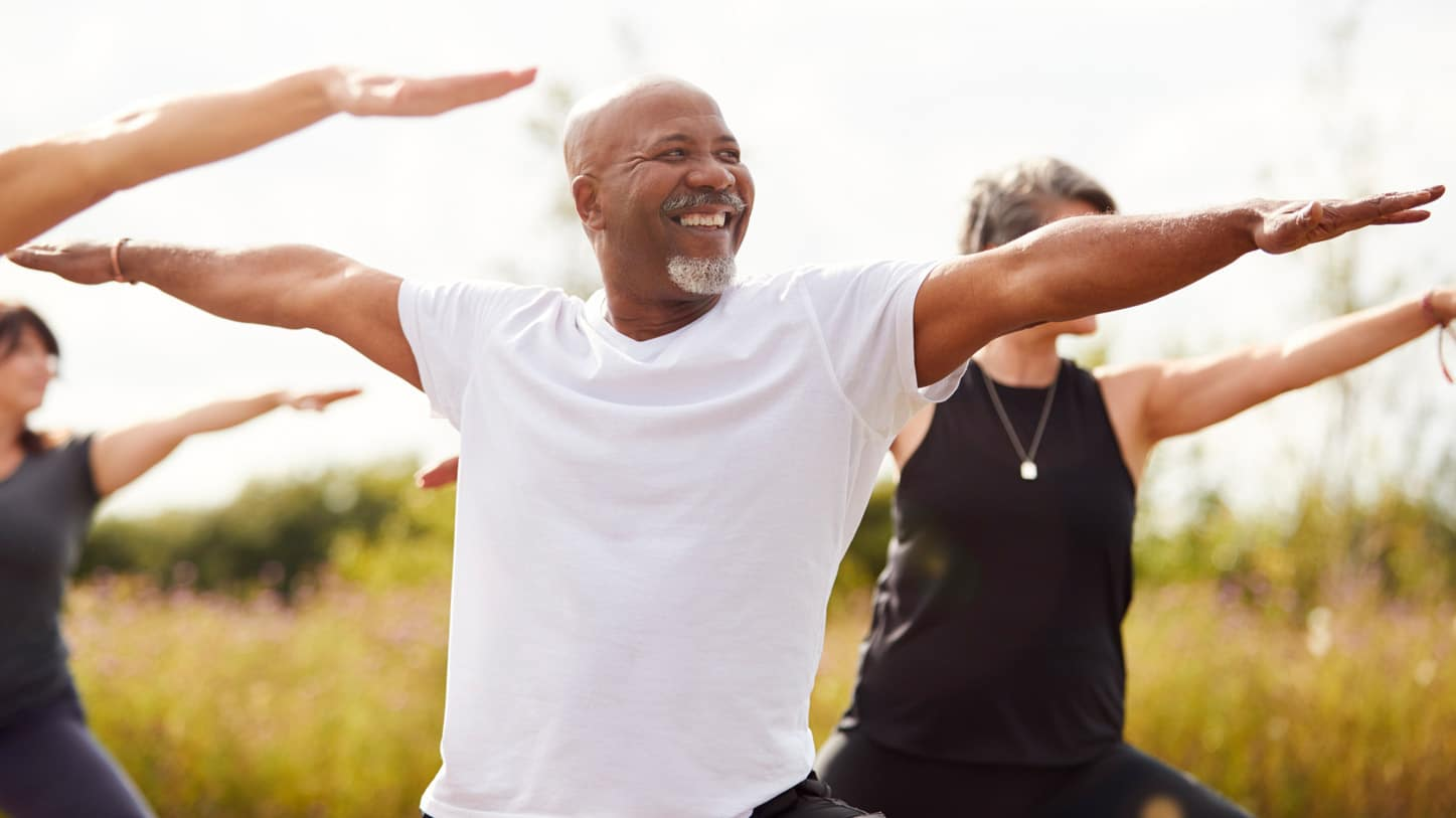 Group Of Mature Men And Women In Class At Outdoor Yoga Retreat